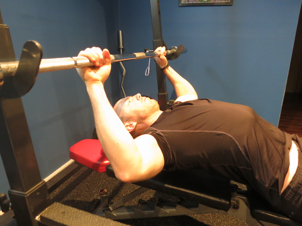 When I am about to begin, I get my grip on the bar, pull my chest up towards the bar, lifting my upper back off the bench, and squeezing my shoulder blades together.
