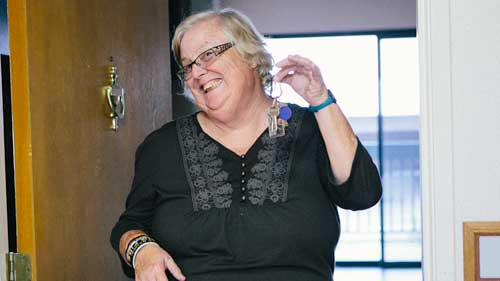 Debbie shows off the keys to her new home acquired through the Home Ownership program.