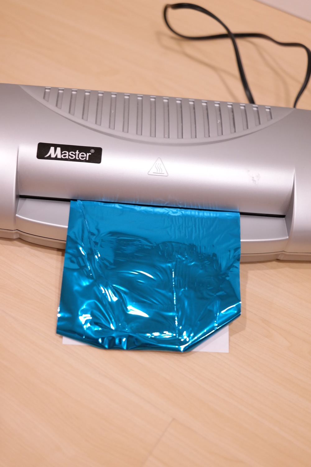 Align the foil on top of the print and run trough laminating machine at least 3-4 times before you peel off the foil
