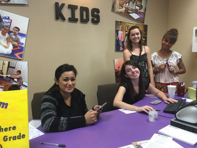 Volunteers at our Kids Center, checking in families