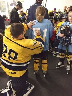 Here, goalie Andrew Santos signs the back of the jersey of one of the girls who plays for the Andover Hockey Association.