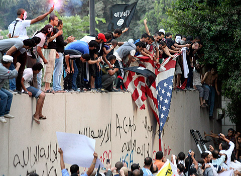 Protesters destroy an American flag pulled down from the U.S. embassy in Cairo.  (Mohammed Abu Zaid/AP)