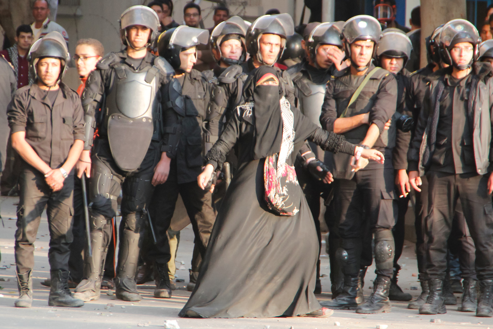 Cairo, Al Qahirah, Egypt -- A woman tries to protect CSF forces from protesters throwing bricks. The photographer claims they said lied in their promise to release her brother. March 5, 2013 (Photo: Bora S. Kamel | Flickr)