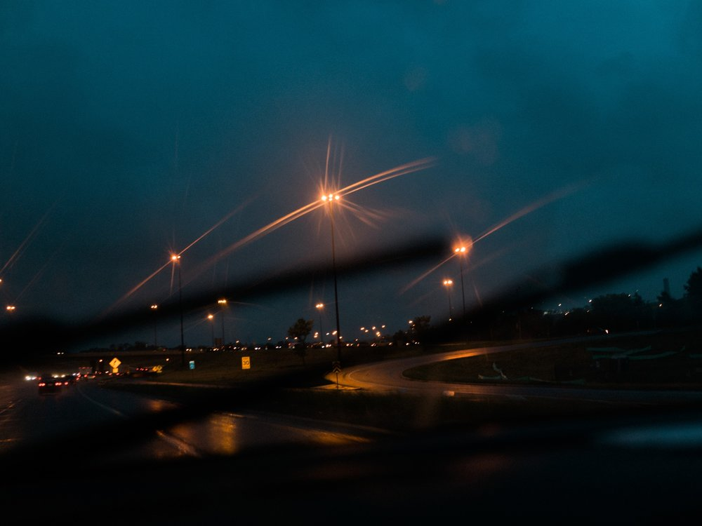 "As part of the ""bring a camera everywhere in August"" thing, I'm also trying to bring my mirrorless camera more places instead of relying on my iPhone. Rain was on my shot list for August and this photo captured the mood of the drive home perfectly (Mazzy Star was playing in the car)."