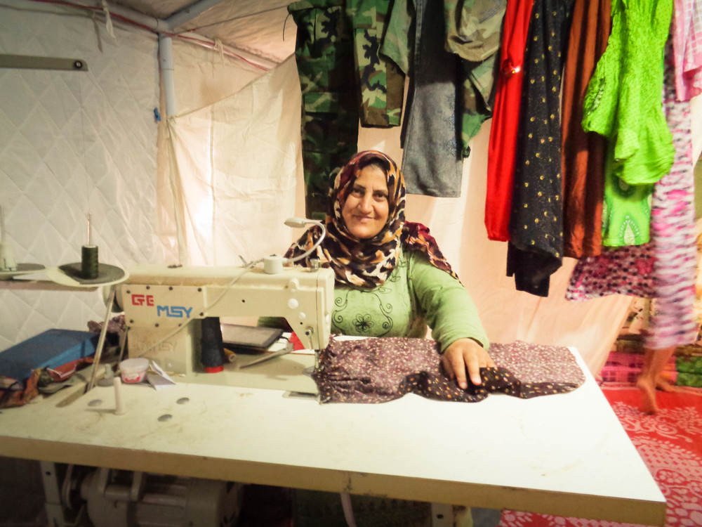 The few people who have ways to earn money, like this woman who sews items for sale, still don't make enough to be self-sufficient.