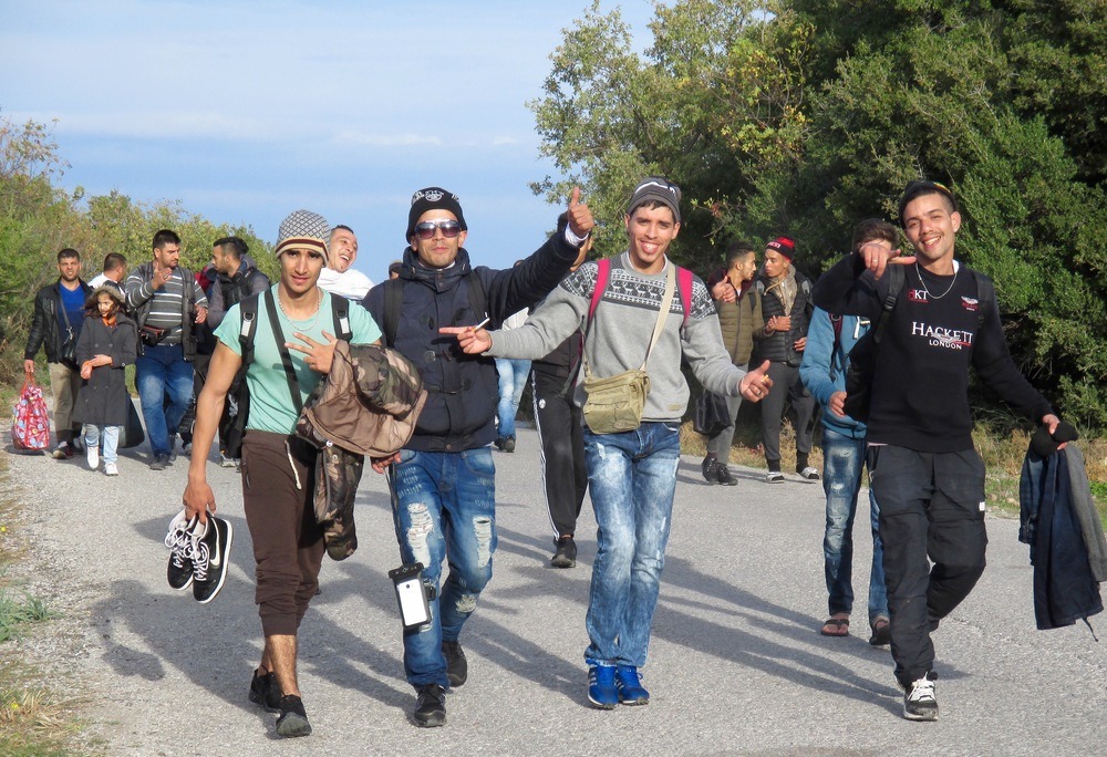 Young men celebrate their arrival into Europe as they walk from the shores of Lesvos to a transit center for processing.