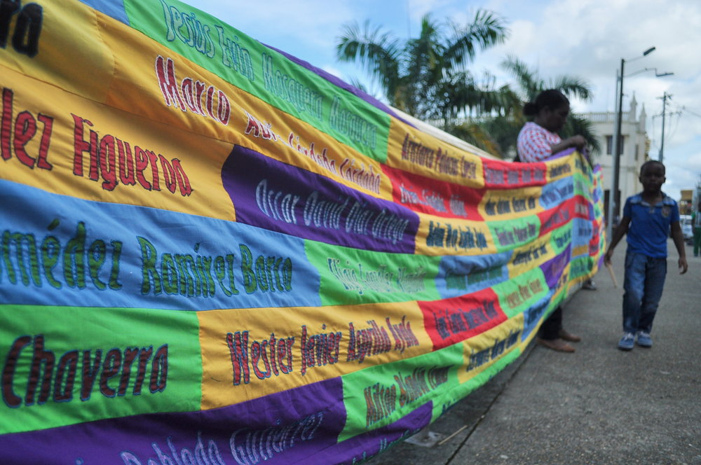This quilt on display during a victims' remembrance vigil includes names of lives lost to the conflict in the department of Chocó.