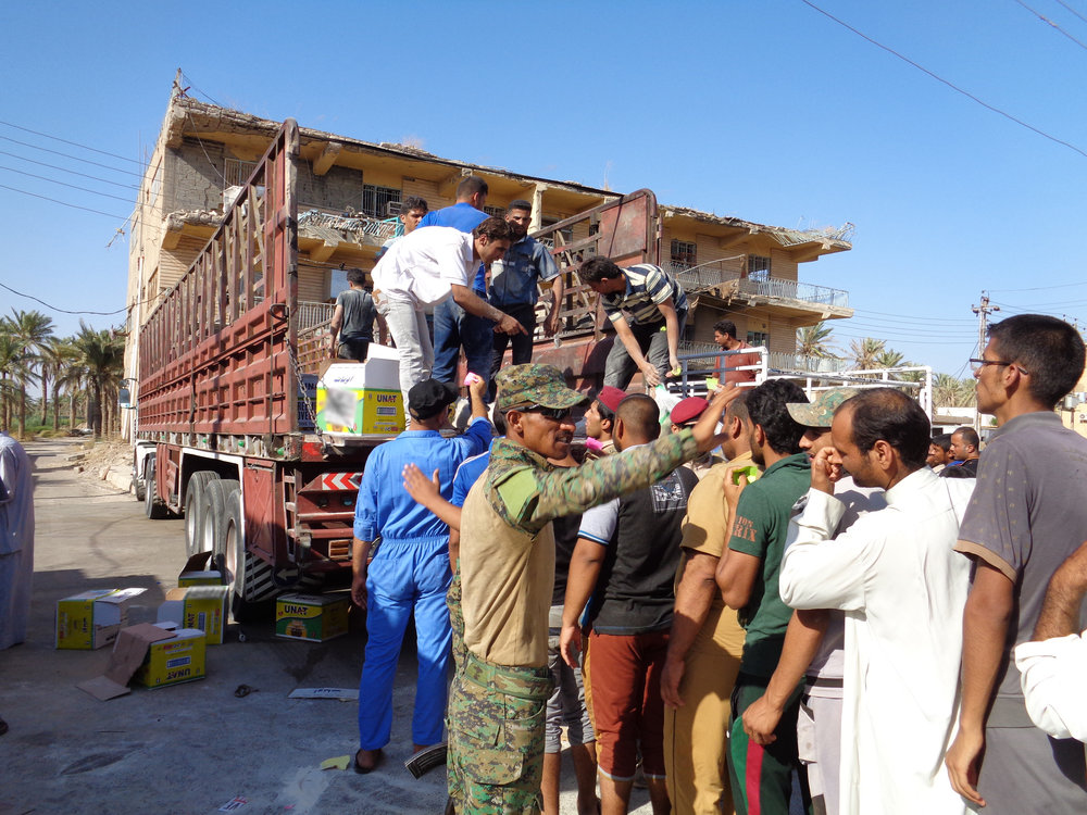 An Iraqi soldier directs the crowd as packages of food and cleaning supplies are handed out. To reach the distribution site, aid agencies have to pass multiple security checkpoints, manned by both Iraqi government forces and militias.