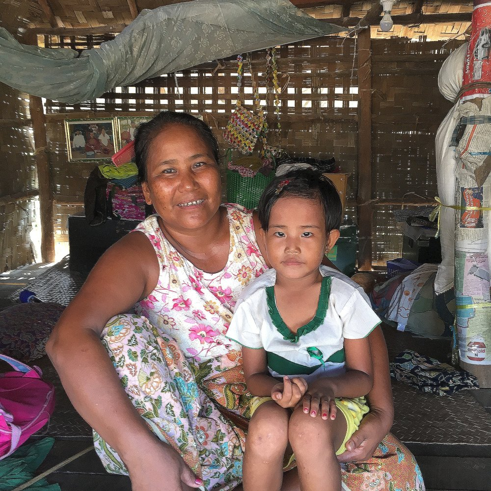 """My husband doesn't live with me and our children because there is no work near our new house.""  In the relocated community of Nansawngpoh, in Sagaing Region, Thu* lives with her three children (her youngest is pictured). After the 2015 flash floods swept away her former village, the government has prohibited Thu and her neighbors from returning and, eventually, relocated them here. Now, in search of income for his family, Thu's husband is forced to live away from the family home, in a tent close to the rice paddies near their old village. Thu explains that following the 2015 floods, it is common for relocated families in her village to live apart in order to try to find work."