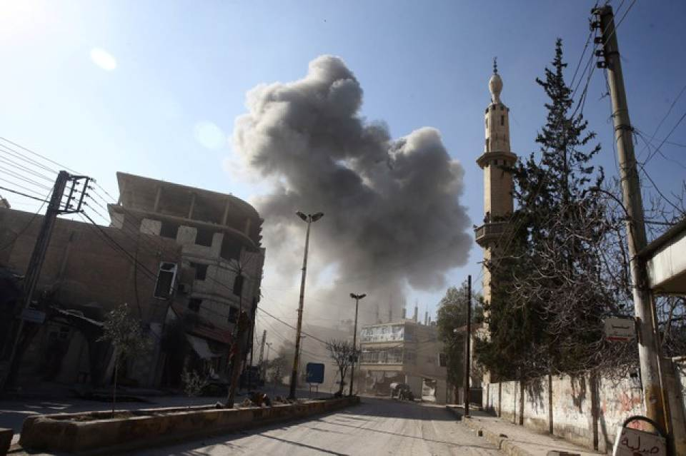Photo Credit: Reuters - Smoke rises from the rebel held besieged town of Hamouriyeh, eastern Ghouta, near Damascus, Syria, February 21, 2018.