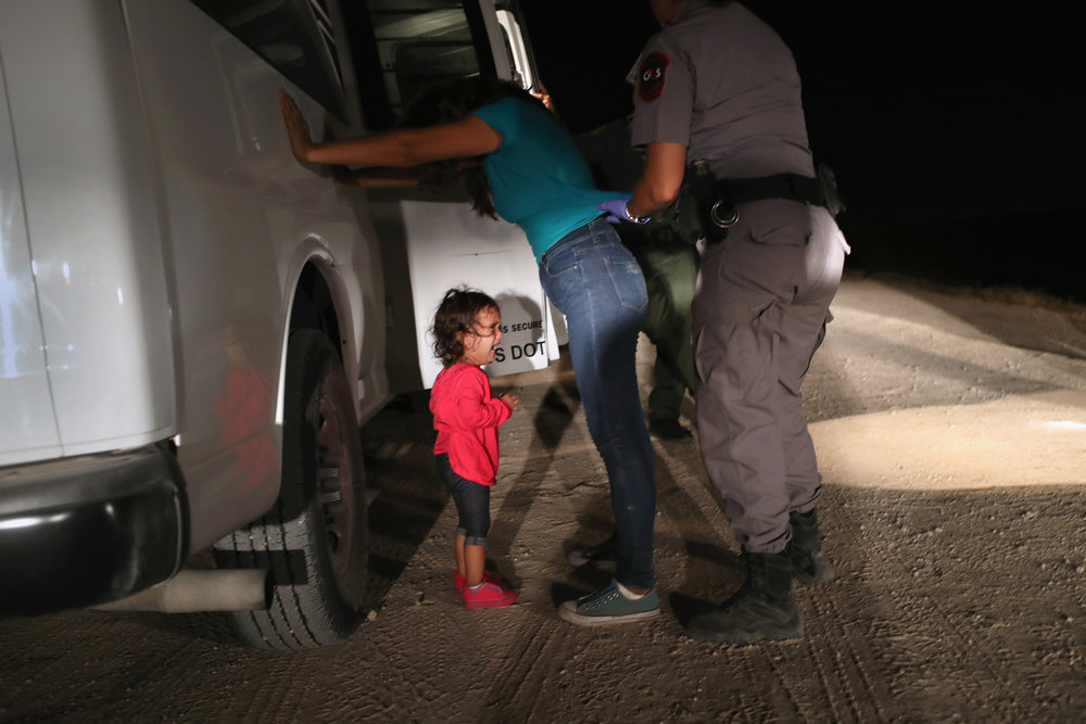 A two-year-old Honduran asylum seeker cries as her mother is searched and detained near the U.S.-Mexico border on June 12, 2018 in McAllen, Texas. (Photo by John Moore/Getty Images)