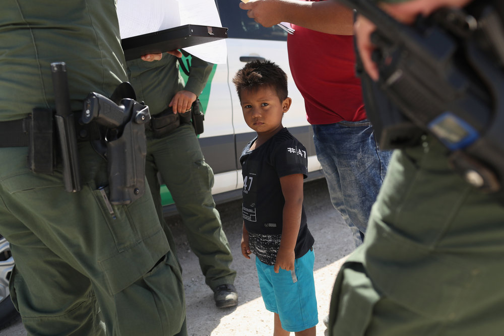 MISSION, TX - JUNE 12: U.S. Border Patrol agents take into custody a father and son from Honduras near the U.S.-Mexico border on June 12, 2018 near Mission, Texas. (Photo by John Moore/Getty Images)