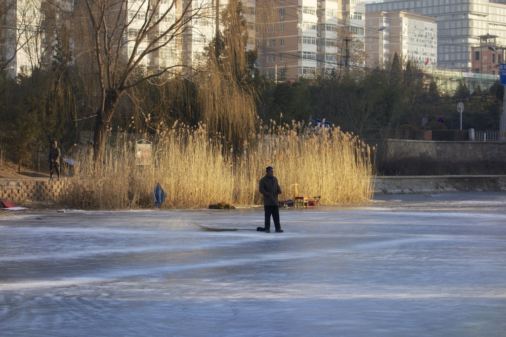 A man with a broom taking a rest from clearing the ice for skaters.