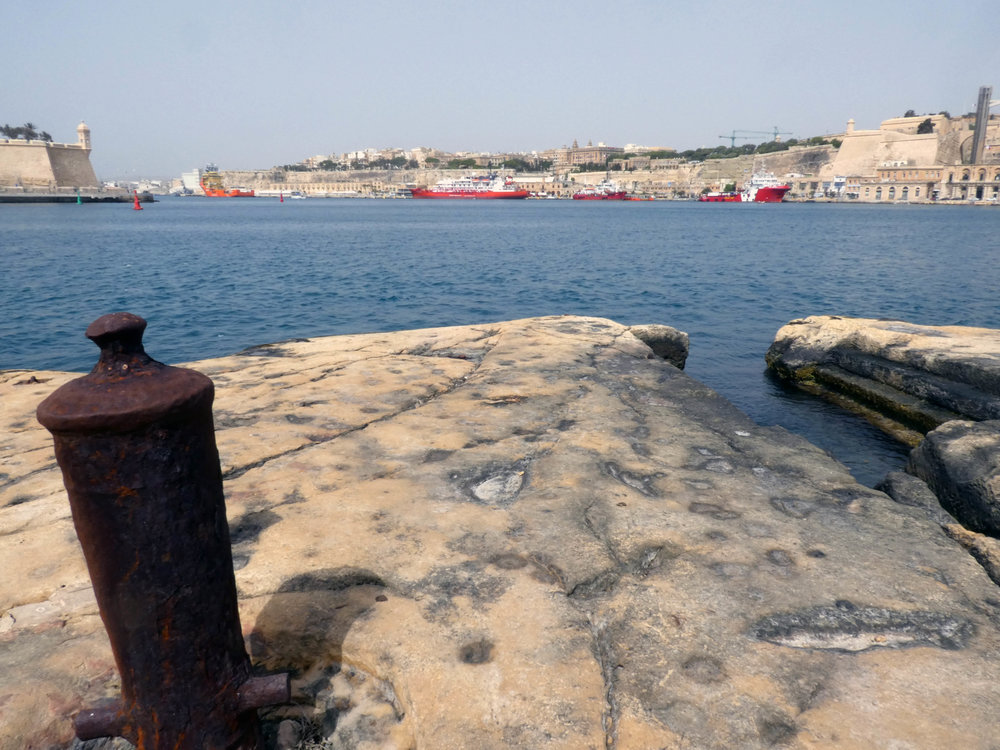 Early view from the base rock of Fort Saint Angelo over to the Valletta Waterfront. Old canons are here often used for the more civil use of fixing ships.