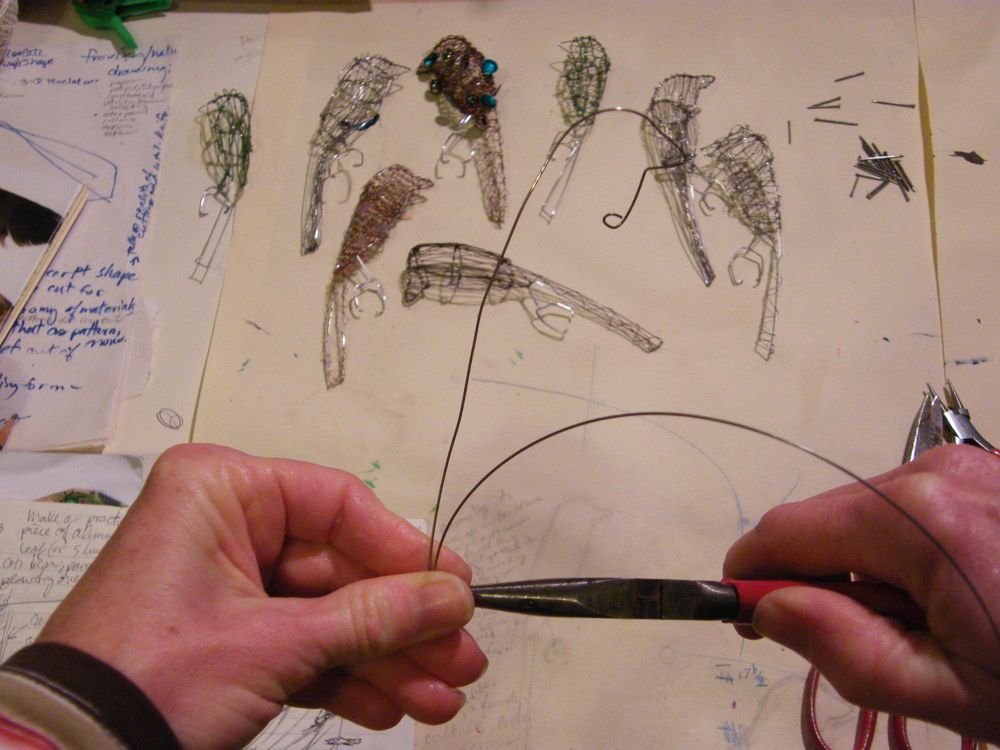 Making wire bird silhouette, completed birds in background.