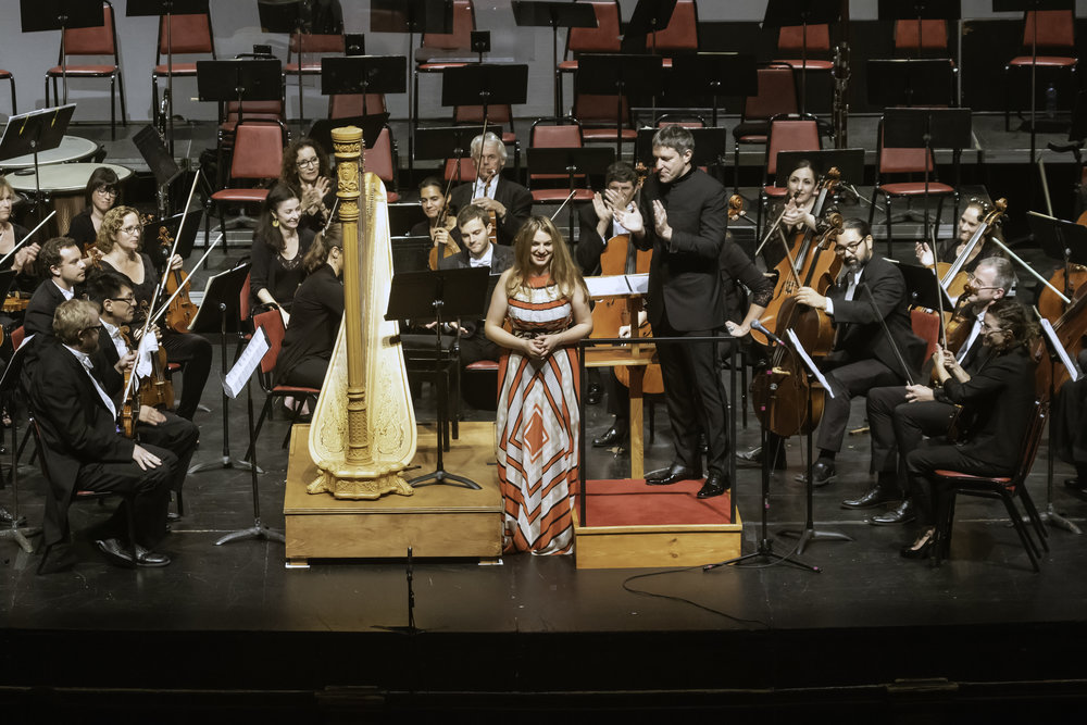 Bridget Kibbey takes a bow after performing Vivian Fung's harp concerto with the New Bedford Symphony Orchestra. Richard Van Inwegen photograph