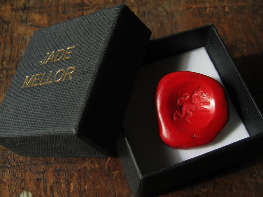 Trompe L'oeil sealing wax button. Polished red resin with a silver shank