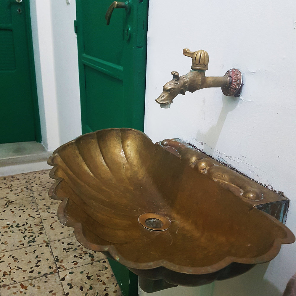 A sumptuous scallop shaped sink outside our room on one our Greek adventures
