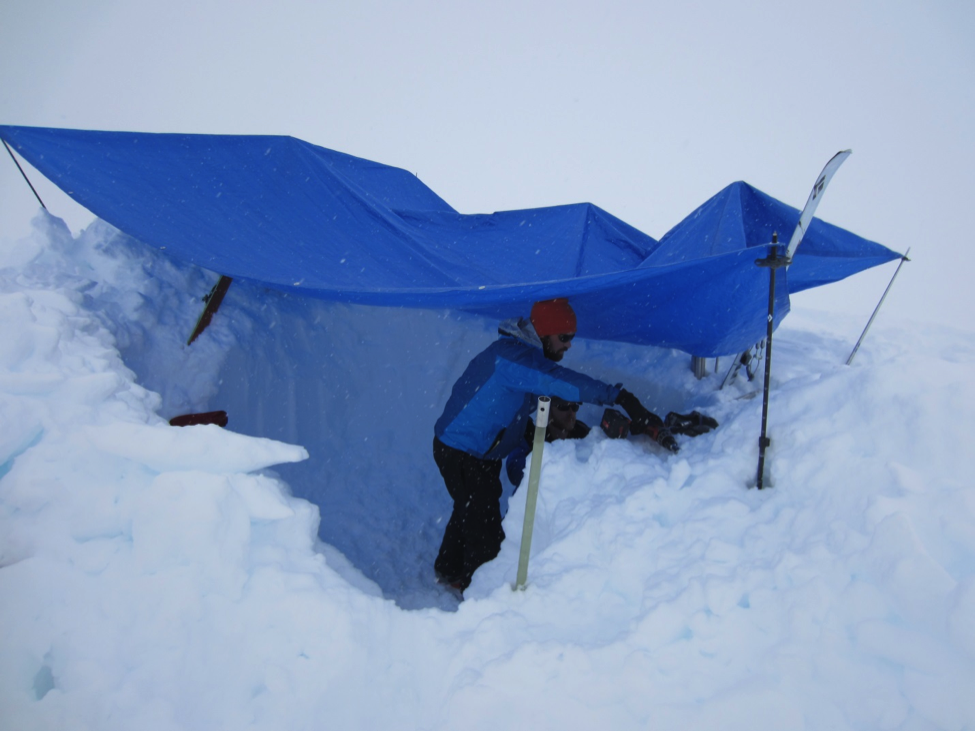 Pat Dryer and Chris McNeil trying to stay out of the weather while drilling a snow core at Taku Glacier snow pit site #4.  Photo:  S. O'Neel