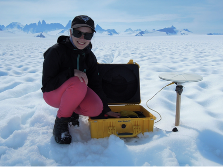 Stephanie Streich by a GPS antenna, mounted to one of the strain gauge stakes. Photo by Jeff Kavanaugh.