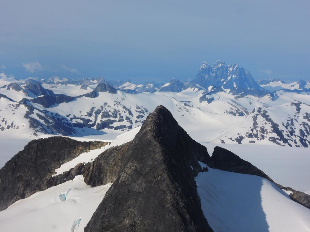 "Devils Paw (in the distance) is the highest mountain on the Juneau Icefield, and the biggest border peak in the region.  Beyond is Canada.  ""From the helicopter it looked like we would touch the side of the mountain in the foreground, we were so close to it.""  Photo by Stephanie Streich"