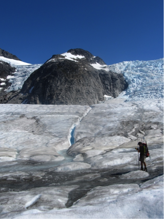 "William Jenkins surveys one of the Gilkey Glacier ogives with GPS.  ""The Cleaver"" is the ridge of rock in the background, with the Vaughan Lewis Icefall on the right.  Photo by Jamie Bradshaw."
