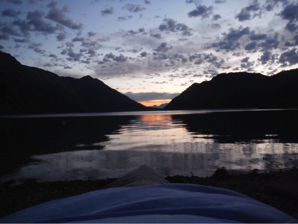 Taken straight from the sleeping bag. The beautiful sunrise over Atlin Lake welcomes us to the day when we return to civilization. Photo by Sarah Bouckoms.