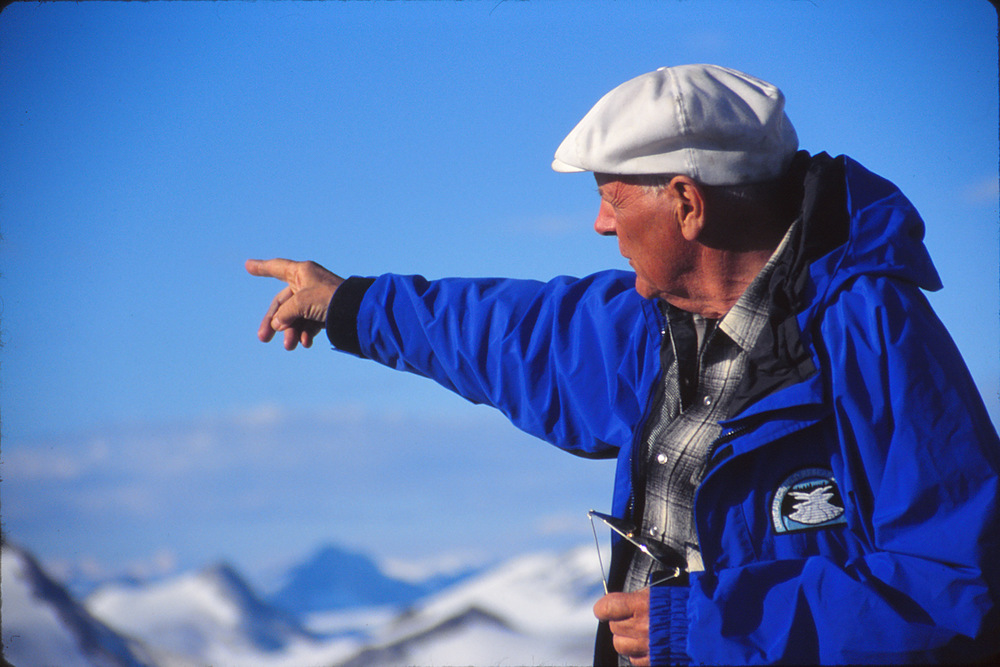"Maynard Miller points to peaks and glaciers of the Juneau Icefield atop ""Taku B"" near Camp 10.  July 1997.  Photo by Matt Beedle."