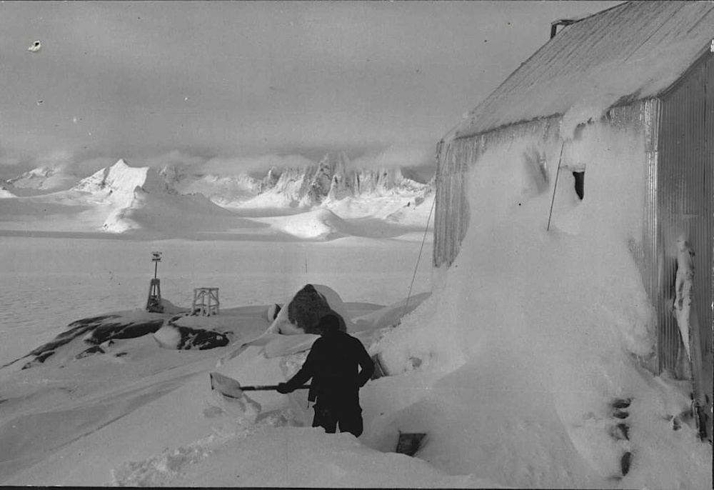 "Maynard Miller shovels out the ""Nunatak Chalet"" - the combined mess hall,  bunk room, radio shack, and storage building that today is the Cookshack at Camp 10. December 1953.  Photo from the FGER Archives."