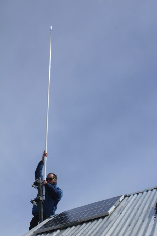 Jon Doty sets the antenna in place. (Photo by Zach Miller)