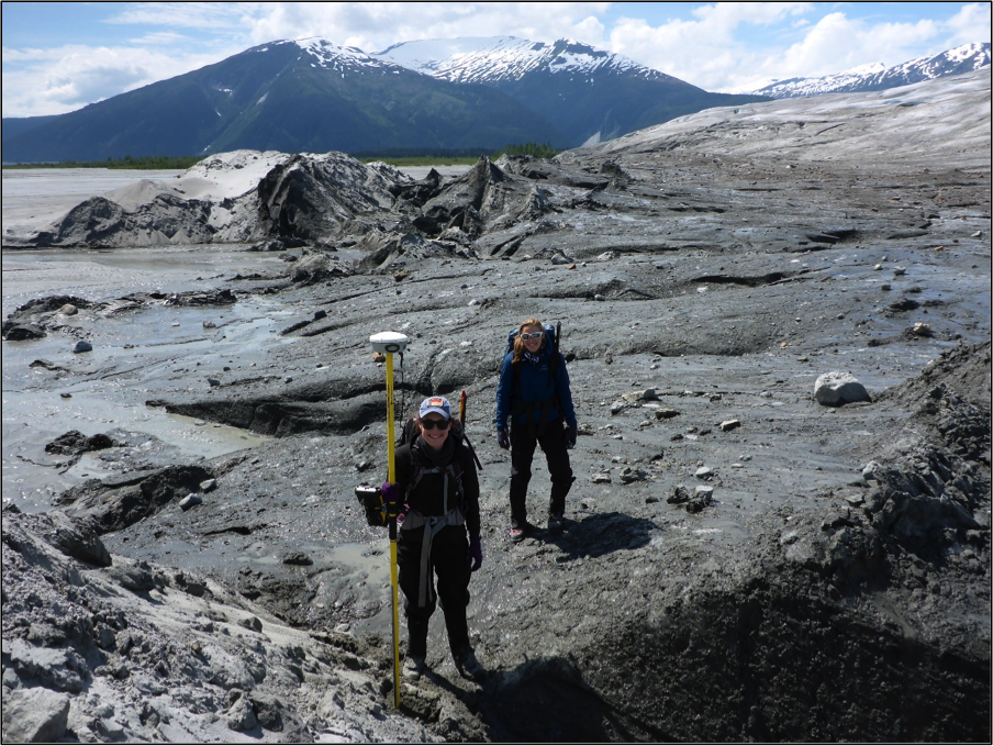 Olivia Truax and Cézy Semnacher taking a GPS point at the boundary between ice and sediment at the terminus of the Taku Glacier.