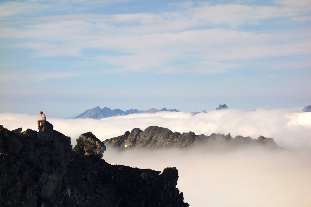 Newt Krumdieck overlooking the cloud-covered icefield from the summit of Mount Moore. Photo by Kenzie McAdams.
