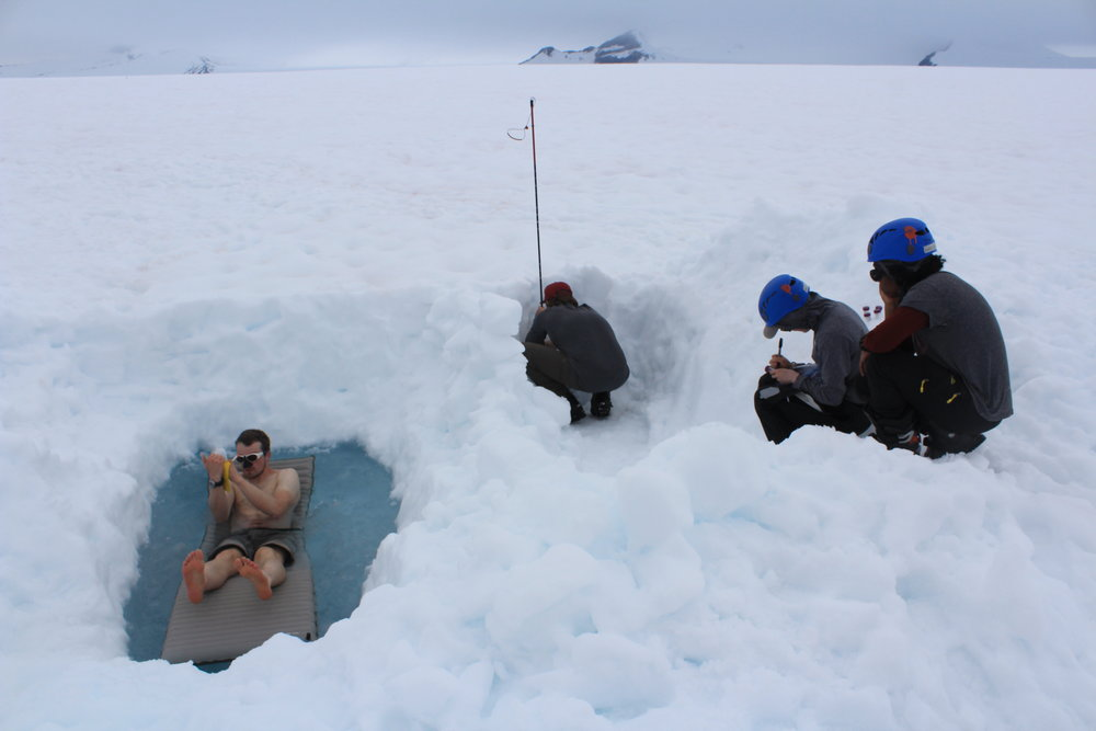 Alex Ihle floats on his therm-a-rest in the pool while recording data in the group field notebook.  JJ Graham takes a snow sample form the pit while Jane Hamel labels sample bottles and Chelly Johnson organizes the samples. Photo credit: Jay Ach.