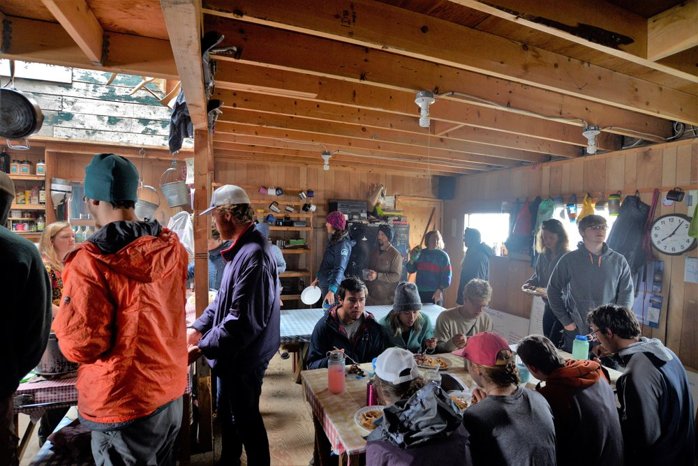 Hungry JIRPers waiting in line for food. With a full camp it takes about 30 minutes for everyone to wind through the breakfast line. The mark of a truly great cook crew is keeping the coffee flowing for the whole process. Photo credit: Jay Ach.