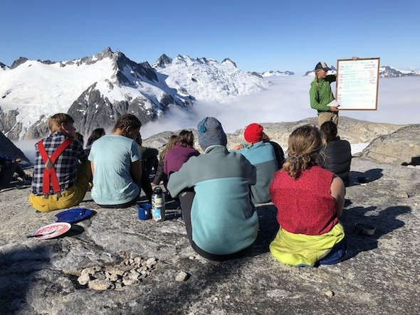 2018 JIRP students and faculty lecture overlooking fog-filled Gilkey Trench at Field Camp 18. Credit: Chip Duncan, Duncan Entertainment Group.