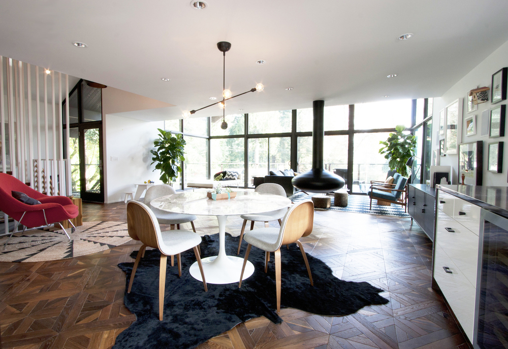 Modern interior design for a home in Portland Oregon. The design includes a Apparatus Highline fixture, Saarinen Dining Table, a red Womb chair and wood parquet floors.