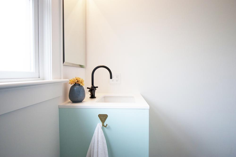 mint vanity with matte black faucet
