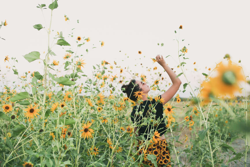 Woman in a field smelling a flower
