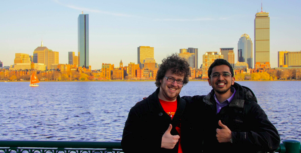 Jason and Muhammed at MIT with the Boston skyline in the background.