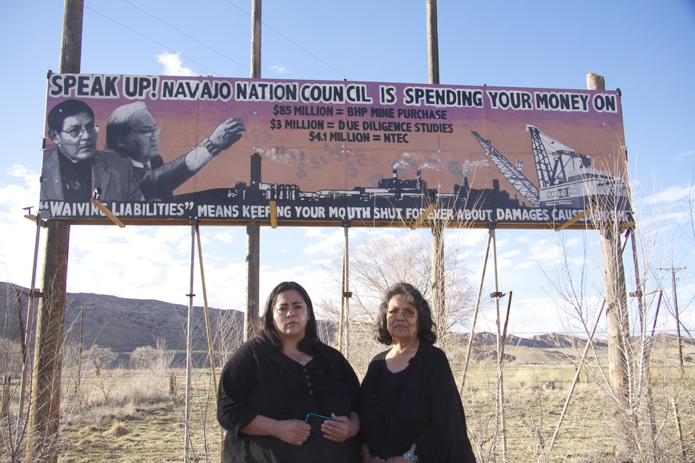 Navajo anti-coal activists Victoria Gutierrez and Sarah Jane White and the billboard they erected on U.S. Highway 64 between Shiprock and Farmington, N.M.