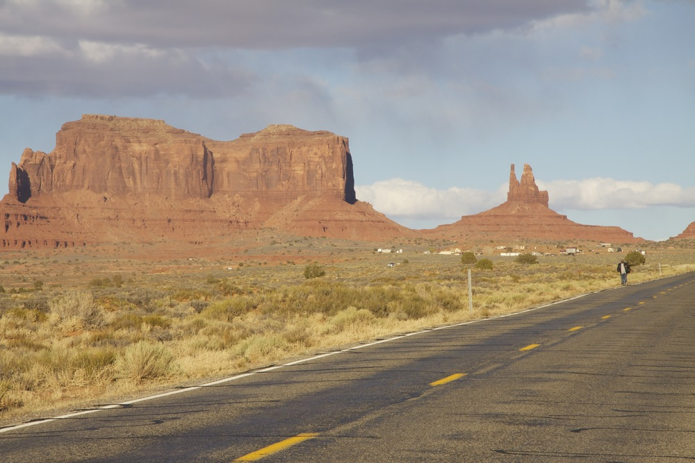 A hitchhiker walking down U.S. 163 in Monument Valley, on the Utah-Arizona border.