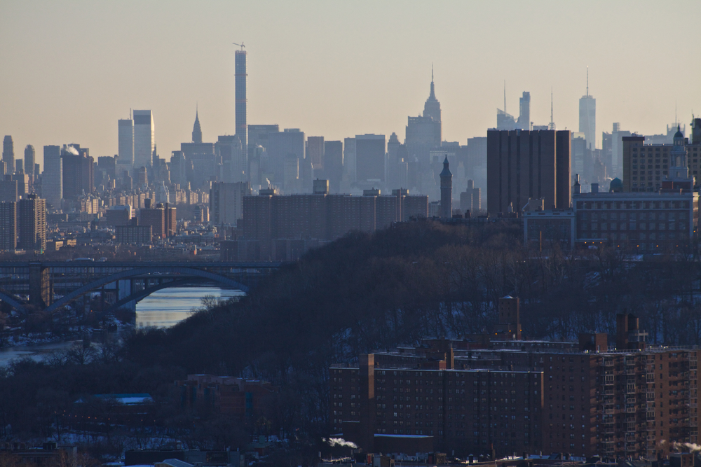 Manhattan before dark on a hazy evening. The Citicorp, Chrysler, 432 Park, Met Life, Empire State, Bank of America and 1 World Trade Center buildings are all visible over the Harlem River and Washington Heights. © Bobby Magill.