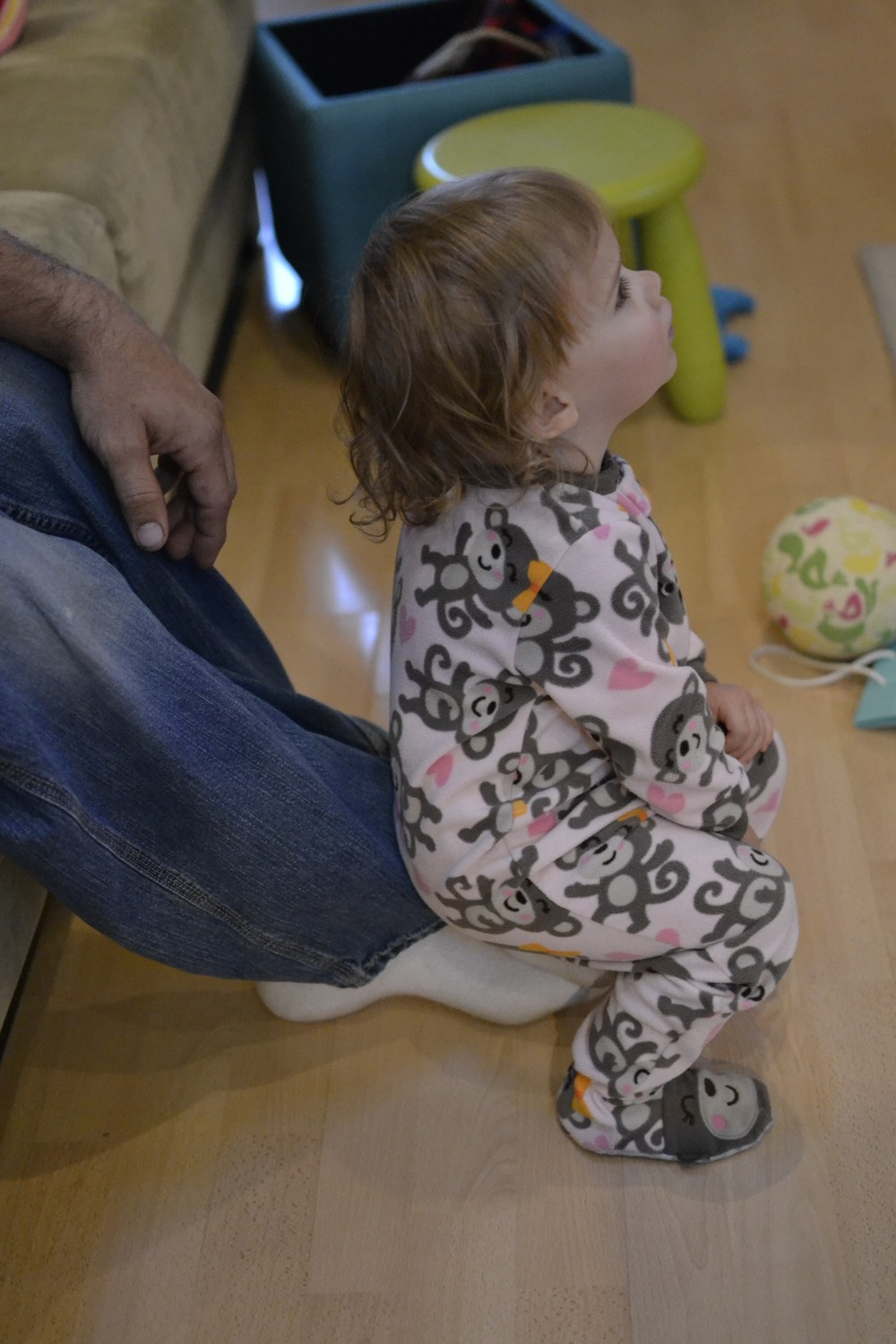 and sitting on daddy's feet while watching