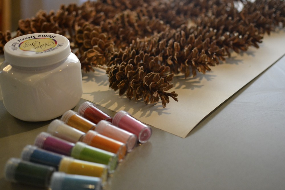 first things first...let's dip and glitter some pinecones!   lay out craft paper over the entire surface you will be working on.  if you didn't purchase a tub of paint, as i did, you can pour your paint into a larger container for dipping.  i found my pinecones while out on a walk and they were still pretty covered in sap.  if this is the case, you might want to wear latex gloves while working with them.