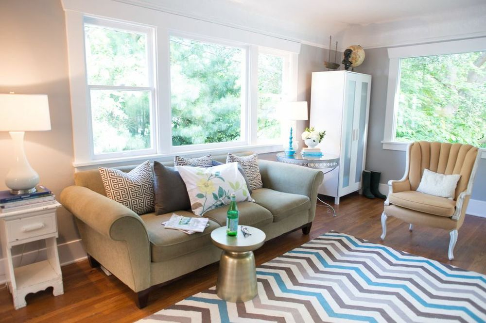 Huge living room that gets tons of light. A chevron rug, vintage tables, reupholstered chairs, brass table, and all the cool things only Keri can assemble complete her adorable home.