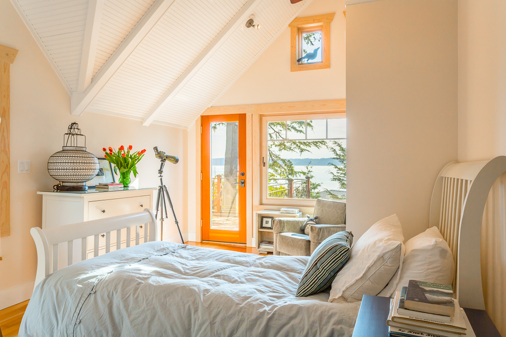 Second upstairs bedroom boasts pitched ceilings in addition to custom loft space and private deck.