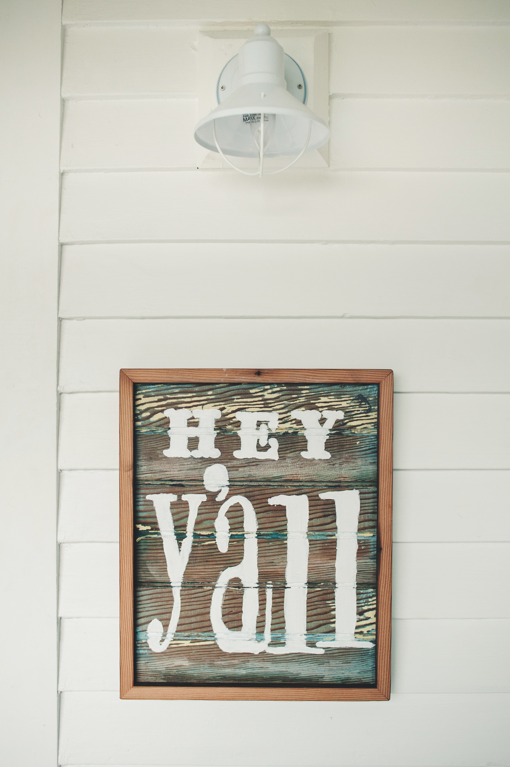 "Keri suggested we take some old bead board that we had already from an old home, and paint the words ""Hey Ya'll"" on it. It's actually pretty perfect. I love the look of the marine cage lights on the white siding. White on white almost always works."