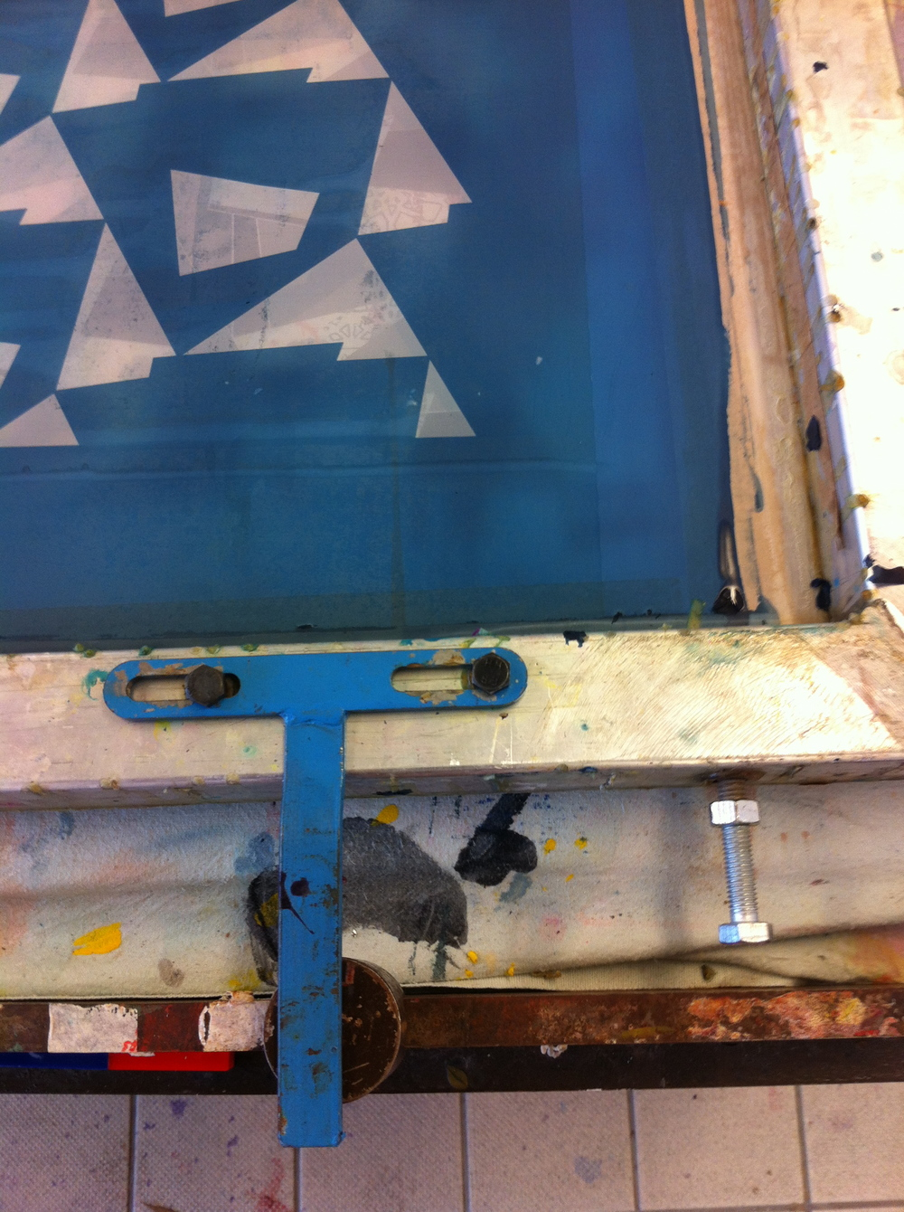 A registration bar is fixed and will be used to align the screen before each print. The repeat is measured by placing the screen alongside the acetates, which tells us the distance required between each stopper. The registration bar will then be used to line up with the stoppers as it is moved along the table.