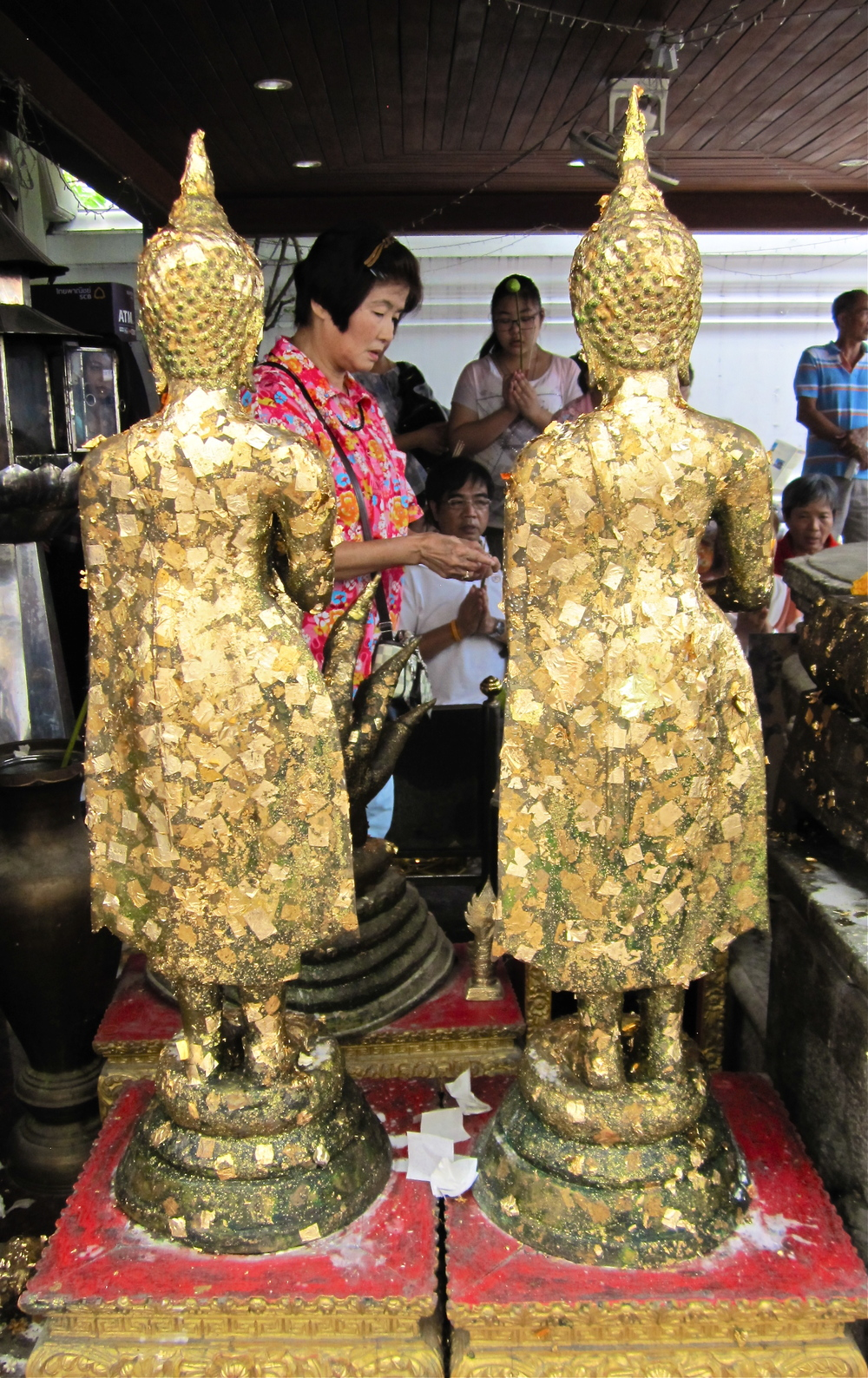 Pieces of gold leaf are placed on stone Buddhas at Wat Pho in Bangkok, Thailand
