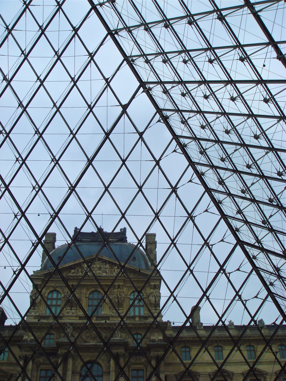 The old, historic building that houses The Louvre in Paris as seen through the front entrance — the infamous modern glass pyramid.